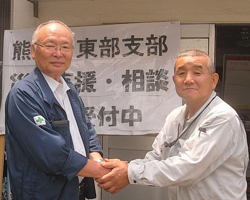 全建総連・三浦委員長(左)と熊本建労・木村委員長(右)が復興に向け固く握手